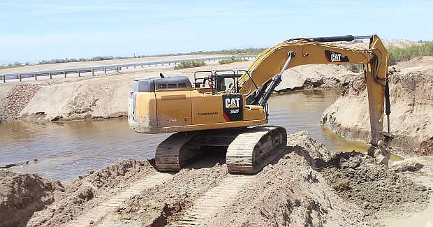 """An excavator removes a piece of dirt to allow water to flow in the """"Big Dig"""" channel."""