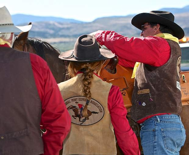 Dwight Borges attaches the mochila to Veronica Jenks' horse 'Bretta' during the 2016 Pony Express Re-ride..