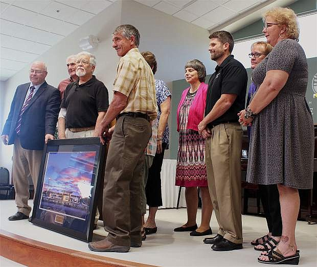A large plaque is presented to the center and Senior Coaliation Board of Directors featuing a photograph by Skip Reeves of Silver State Photography; on the far right is senior center Executive Director Lisa Erquiaga.