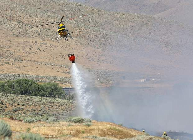 A helicopter drops a bucket of water on to a wildland fire north of Genoa.