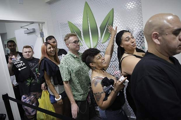 People wait in line at the Essence cannabis dispensary, Saturday, July 1, in Las Vegas.