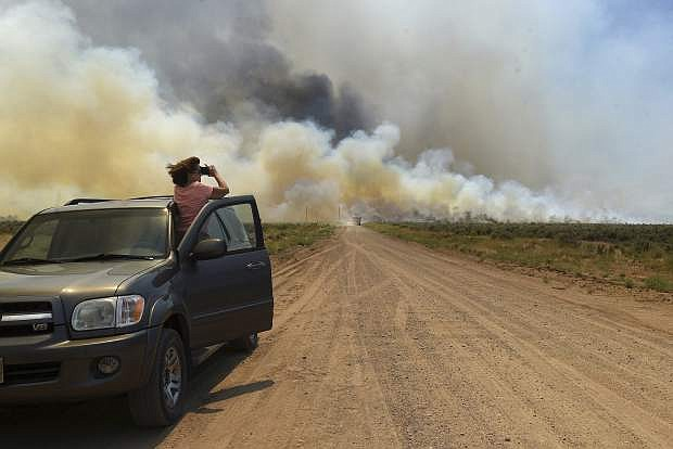 Tamara Pearce watches as a wildfire rages over a private property in the Palomino Valley, Wednesday, July 5, 2017, near Reno, Nev. A day after beating back flames to prevent damage to dozens of rural homes, fire officials on Wednesday advised more residents to evacuate with their animals ahead of one of several blazes sweeping across hot, dry northern Nevada rangelands. (Jason Bean/The Reno Gazette-Journal via AP)