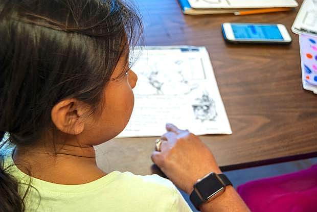 "Alice Wrenn, an in-school tutor for the RSIC Education department, follows along with a student on June 21. ""I love my job, I love working with my kids everyday, and I love teaching my kids to love to learn,"" she said."