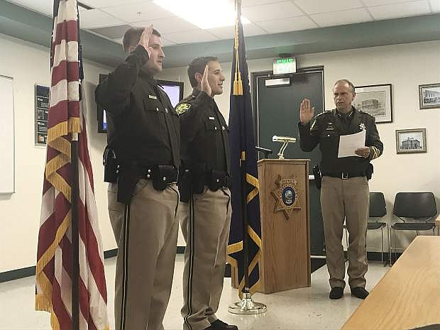 Deputy James Foster and Deputy Maxwell Macedo stand to take their oath of office as they are sworn into the Carson City Sheriff's Office Friday.