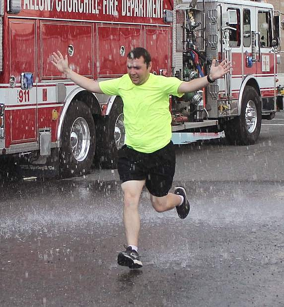 Sean Lacow runs through a spray of water as he homes to the finish of the Honoring American Heroes 5k.