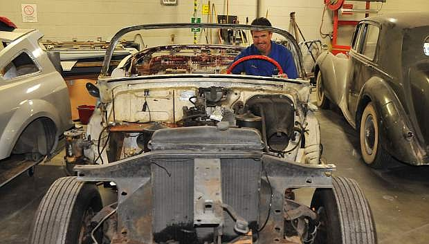 Western Nevada College Automotive Mechanics instructor Jason Spohr sits behind the wheel of a 1953 Cadillac convertible that a new auto restoration class will continue restoring this fall.