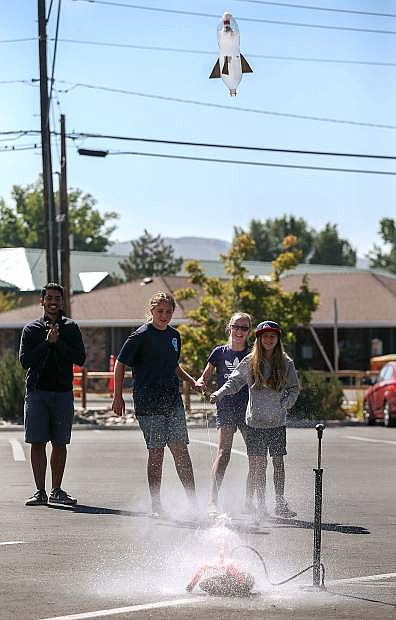 Omar Embaby, with Spokes Across America, watches as Ella Wick, Katie Schulze, both 12, and Eyden Nicholas, 10, launch their water rocket at the Carson City Library in Carson City, Nev., on Thursday, Aug. 10, 2016. Spokes Across America is a team of MIT and Harvard students who bike across the country teaching STEM skills at schools, libraries and camps.