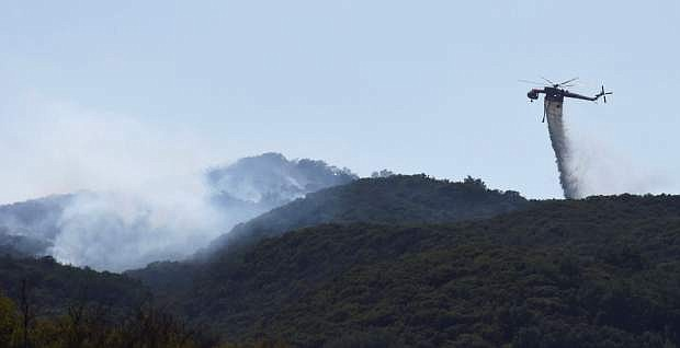 In this photo provided by the Santa Barbara County Fire Department, a Skycrane makes a water drop on hot spots near Hot Spring Canyon and Highway 154 in the Whittier fire area near Santa Barbara, Calif., Wednesday, July 12, 2017. In Southern California, thousands of people remained out of their homes as a pair of fires raged at different ends of Santa Barbara County. The fires broke out amid a blistering weekend heat wave that toppled temperature records. (Mike Eliason/Santa Barbara County Fire Department via AP)