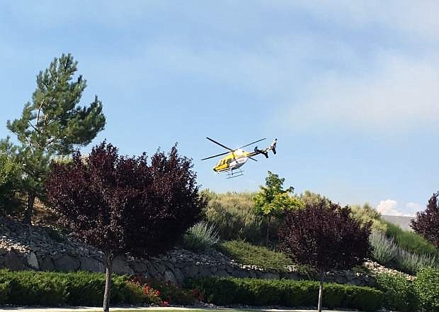 A helicopter dips water out of a pond on the Genoa Lakes Ranch Course north of Genoa on Monday.