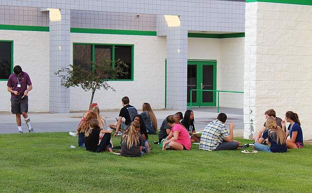 LEAD Green youth gather outside at CCHS to enjoy Pizza Barn pizza on a break between speakers.
