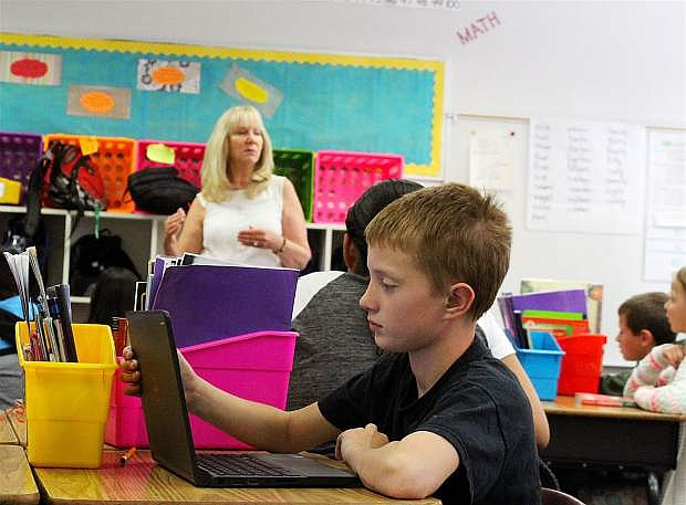 Adam Blunt, a fourth-grade student at Numa Elementary last year, studies a lesson from teacher Pat Moore on a laptop last spring.
