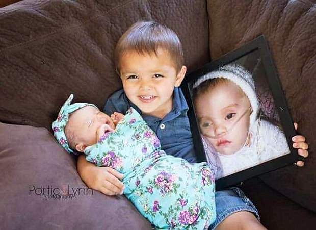Anakin Garcia holds both of his sister:, Wren, left, whom is battling Vanishing White Matter, and a photo of Winter, right, whom died from VHM at 8 months old.