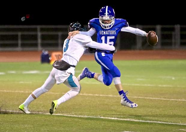Sophomore quarterback Jon Laplante is wrapped up by a North Valleys player Friday night at Carson High.