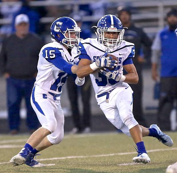 Jon Laplante hands the ball off to Kyle Rudy Friday night against McQueen in Reno.