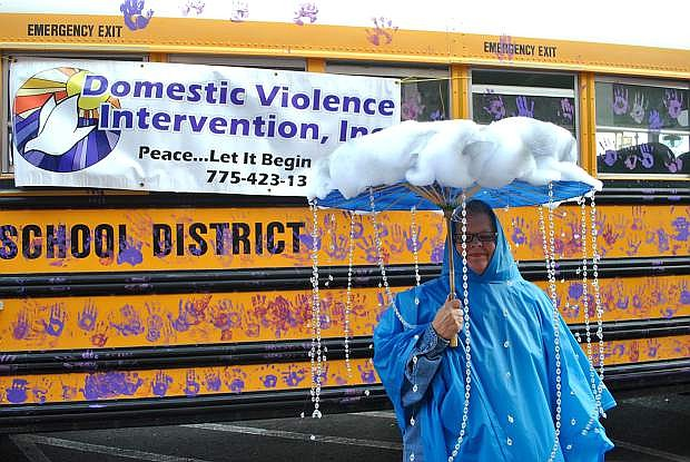 """Karen Moessner, director at Domestic Violence Intervention, stands peacefully in her last year's Halloween attire for the downtown """"Trick-or-Treat"""" event, posing in front of the CCSD school bus decorated with student handprints teaching """"hands are not for hitting."""""""