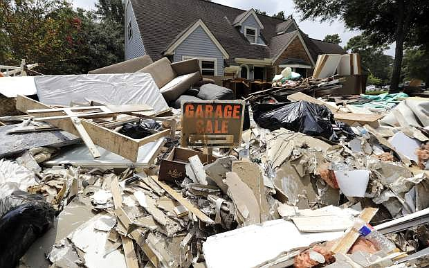 A garage sale sign stands in a pile of debris damaged by floodwaters in the aftermath of Hurricane Harvey Sunday, Sept. 3, 2017, in Spring, Texas. (AP Photo/David J. Phillip)