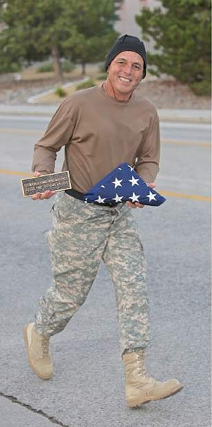 Ken Curtzwiler carries a flag and plaque in rememberance of his daughter SFC Miranda McElhiney during the IHOP Memorial Run/Walk Wednesday morning.