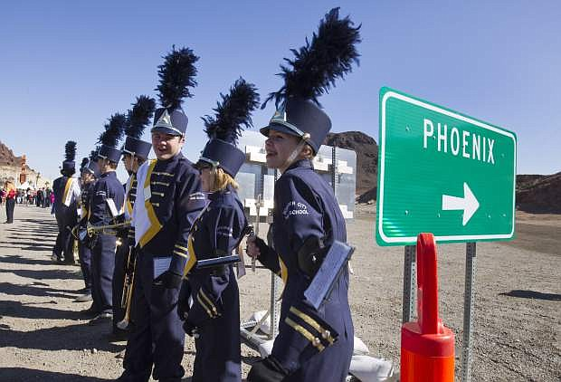 Piccolo player Grace Priest, right, and other members of the Boulder City High School marching band, wait for the start of a groundbreaking ceremony for the Interstate-11/Boulder City Bypass project near Boulder City, Monday, April 6, 2015. The $318 million project is expected to be completed in 2018 and create about 4,000 jobs. (Steve Marcus/Las Vegas Sun via AP)