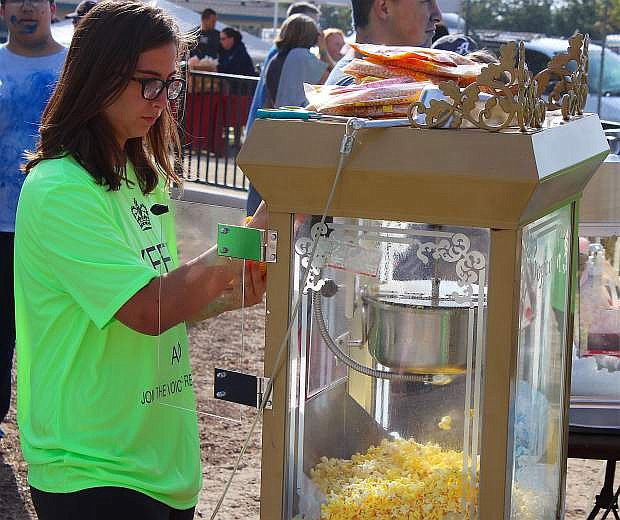 """JROTC member and volunteer Kailey Freeman, a freshman at Churchill County High School, helps ready the group's popcorn machine. The JROTC students have helped before and also assisted with the color blast run. """"I love this,"""" Freeman said of the event."""