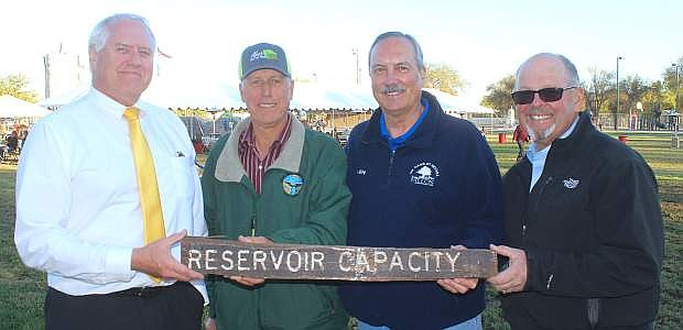 A sign indicting full capacity at Lahontan Reservoir was found floating on top of the water and was presented to the Truckee Carson Irrigation District. From left are Rusty Jardine, TCID's general manager; Ernie Schank, president of the TCID board; Fallon Mayor Ken Tedford and County Commission Chairman Pete Olsen.