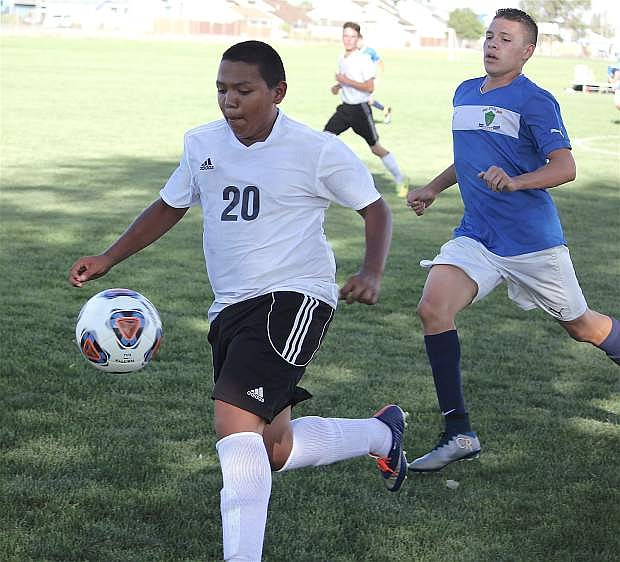Fallon's Dionisio Lopez races the ball ahead of one of Lowry's players.