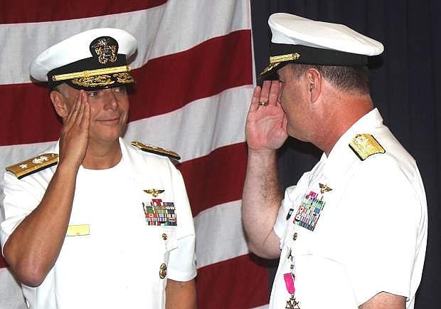 Outgoing commander of the Naval Aviation Warfighting Development Center, Rear Adm. Mark Harris, right, salutes incoming commander, Rear Adm. Daniel Cheever.