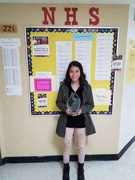 Gloria Valdenegro, a Carson High School sophomore and National Honor Society Officer, stands in front of the blood donation sign-up board holding last year's challenge competition trophy.