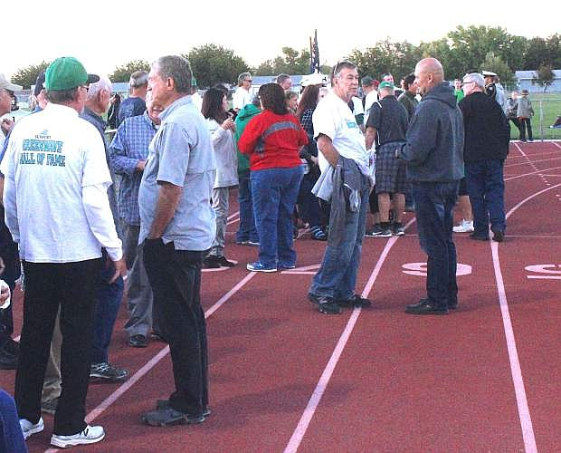 Hall of Fame inductees chat prior to being introduced at the homecoming football game.