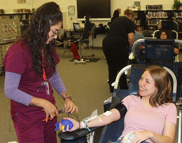United Blood Service technician Raelena Valenzuela, left, prepares Churchill County High School student Angelina Mattern to give blood Wednesday morning.