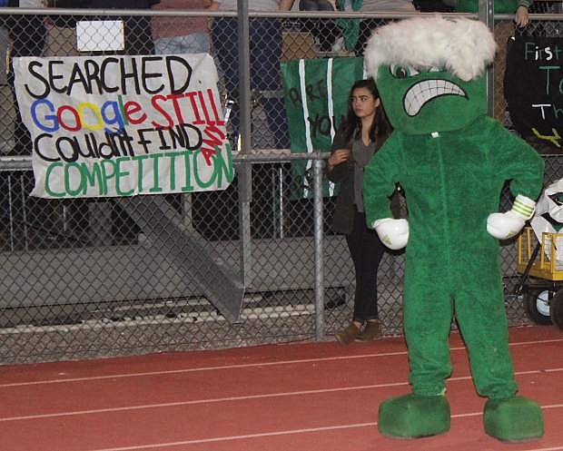 The Greenwave mascot appears before a homecoming sign.