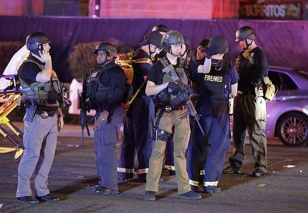Police officers stand at the scene of a shooting near the Mandalay Bay resort and casino on the Las Vegas Strip, Monday, Oct. 2, 2017, in Las Vegas. Multiple victims were being transported to hospitals after a shooting late Sunday at a music festival on the Las Vegas Strip. (AP Photo/John Locher)