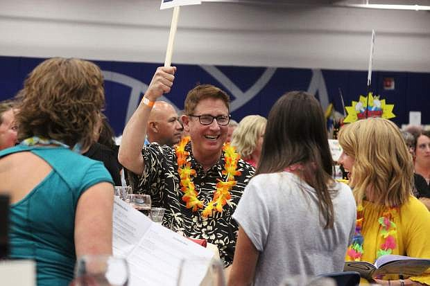 Bill Calhoun raises a paddle during the live auction, one of the most popular and enduring events at the Boys & Girls Clubs of Western Nevada Luau each year. The live auction portion of the event raised well over $60,000 this year.