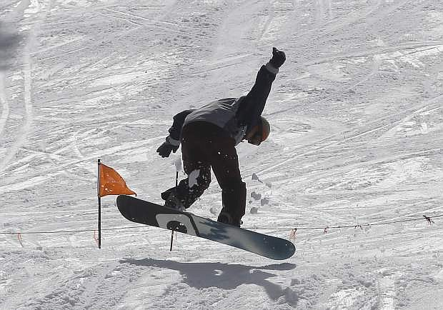 FILE - In this Tuesday, March 1, 2016, file photo, a snowboarder takes a jump at the Sierra-at-Tahoe Ski Resort near Echo Summit, Calif. The ski and snowboard industry is healthy, at least for now. But there is concern throughout the snow sports industry as the baby boomers and generation Xers get older, the millennials are not picking up the slack and hitting the slopes as often as the aging generations. (AP Photo/Rich Pedroncelli, File)