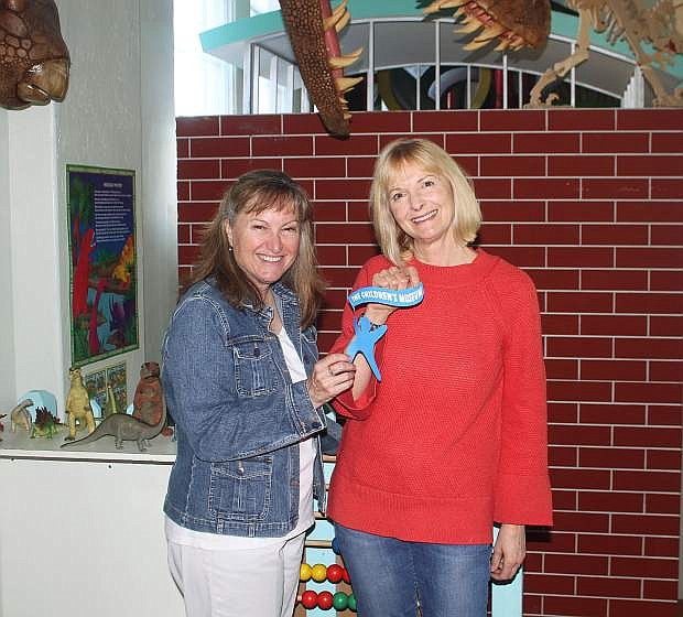 Luana Olsen welcomes new Children's Museum executive director Beth Ellis with the passing of the museum's logo, Carson.