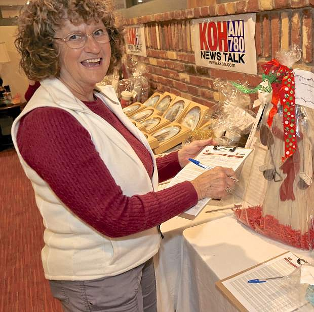 Karen Allen of Carson City bids on a silent auction item at the Salvation Army Red Kettle Kickoff at the Max Casino Friday.