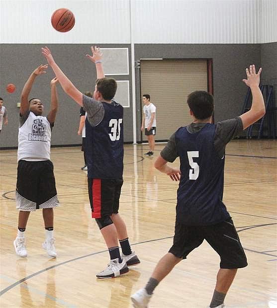 Marcus Dahl (in white) passes the ball to Joshua Mikulak over Ryan Jones' head.