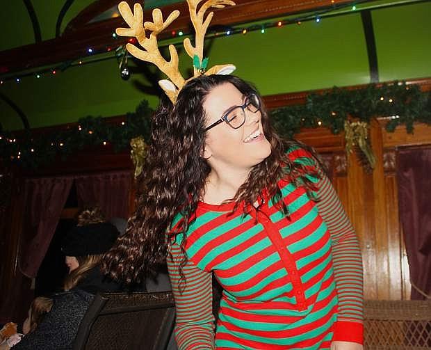 Clad in pajamas and reindeer antlers, Kenzie Bales sings Christmas carols aboard the Polar Express.