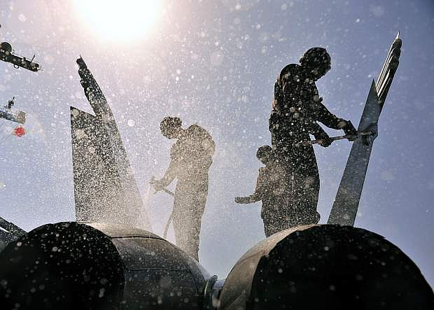 Sailors perform a fresh-water wash down on an F/A-18F Super Hornet attached to the Fighting Black Lions of Strike Fighter Squadron (VFA) 213 aboard the aircraft carrier USS George H.W. Bush (CVN 77).