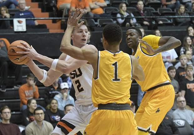 Oregon State's Drew Eubanks looks for an open teammate as Wyoming's Justin James (1) and a teammate defend during Monday's game in Corvallis, Ore. Wyoming won, 75-66.