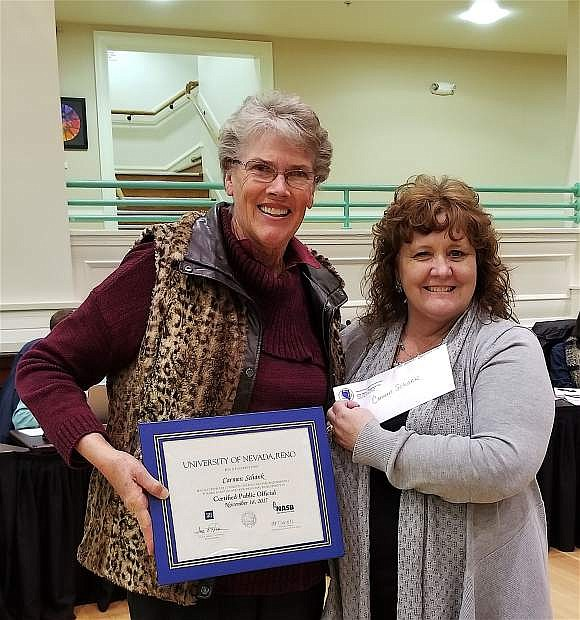 Assistant Director at University of Nevada, Reno's Extended Studies, Shera Alberti-Annunzio, right, presents Trustee Carmen Schank, left, her certification for Professional Development at the scool board meeting last week.