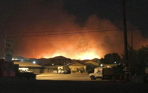 Flames from a wildfire loom up over a neighborhood in Santa Paula, Calf., Monday, Dec. 4, 2017. Ventura County fire officials say the blaze broke out Monday east of Santa Paula, a city of 30,000 people about 60 miles northwest of downtown Los Angeles. Powerful winds are pushing the blaze west toward the city along Highway 150, which is shut down. (Megan Diskin/The Ventura County Star via AP)