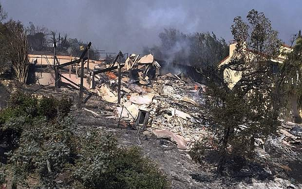 Bob Pazen's home is a smoldering ruin after after a wildfire swept through Ventura, Calif., Tuesday, Dec. 5, 2017. Pazen was in bed Monday night when his son came in and told them they needed to evacuate. Pazen, his wife, son and the family dog evacuated from the home, grabbing just a few pieces of clothing and jewelry. When he came back to check on his home Tuesday morning, his house was fine, but when he returned later, the house was fully engulfed in flames. (AP Photo/Amanda Lee Myers)