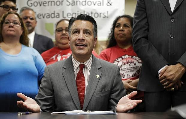 FILE - In this June 15, 2017, file photo, Nevada Gov. Brian Sandoval speaks before signing Senate Bill 539 during a signing ceremony in North Las Vegas, Nev. State officials and medical administrators are starting a new prescription medication registry early January 2018 designed to fast-track information collection about opioid deaths and identify excess dispensing of powerful painkillers. The effort enacts provisions of Assembly Bill 474, which was proposed by Sandoval and unanimously passed the Legislature this year. (AP Photo/John Locher, File)