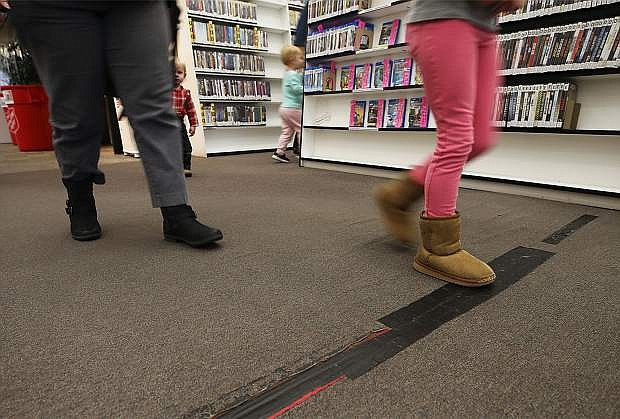Patrons walk over patched sections of carpet at the Carson City Library in Carson City, Nev., on Thursday, Nov. 30, 2017. The library will close on Dec. 10 for up to eight weeks while crews install new flooring and paint the interior. Photo by Cathleen Allison/Nevada Momentum