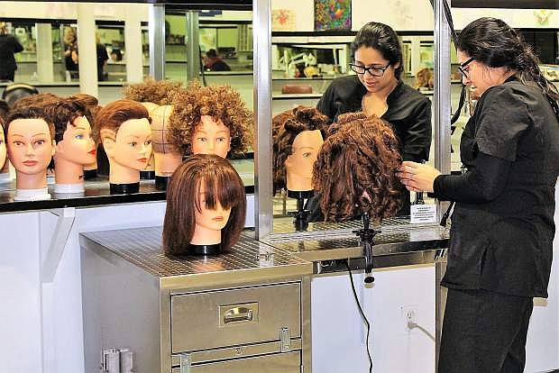 Sierra Academy of Style freshman student Gaby works on a mannequin head to learn styling and cutting skills.