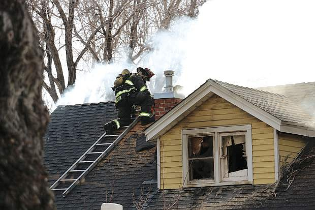 Carson City Fire Capt. Scott Baker climbs the roof of a residence to help contain an arson fire at Sixth and Minnesota.