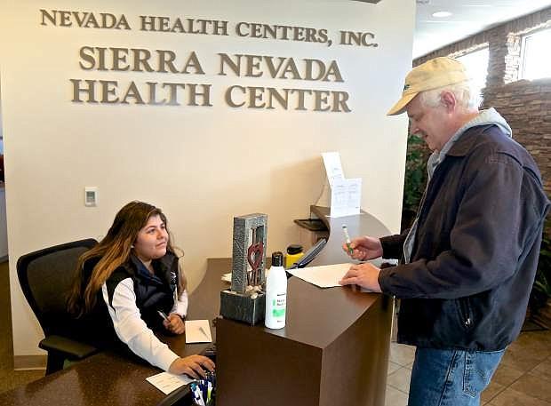 Front office receptionist Karen Becerra checks in Mark A. at the Sierra Nevada Health Center Thursday.
