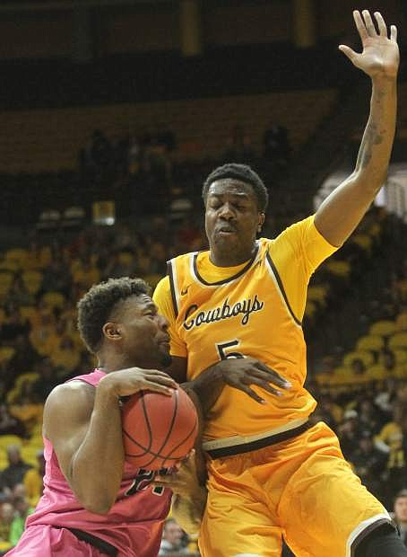 Nevada forward Jordan Caroline (24) bumps up against Wyoming forward Alan Herndon (5) during the first half of an NCAA college basketball game in Laramie, Wyo., Wednesday, Jan. 24, 2018. (Shannon Broderick/Laramie Boomerang via AP)