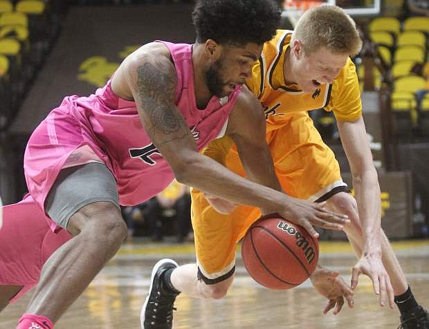 Nevada forward Elijah Foster (12) and Wyoming forward Hayden Dalton (20) scramble for the ball during the first half of an NCAA college basketball game in Laramie, Wyo., Wednesday, Jan. 24, 2018. (Shannon Broderick/Laramie Boomerang via AP)