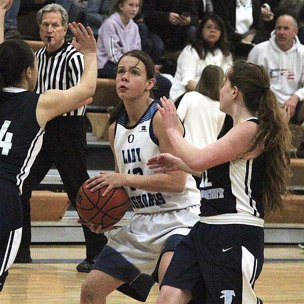 Oasis's Janelle Pike readies to shoot a basket around Kailya Dowling of the Lady Falcons.